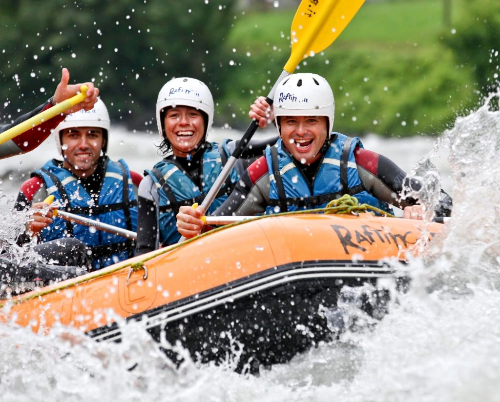 Three rafters smiling into the camera while paddling.