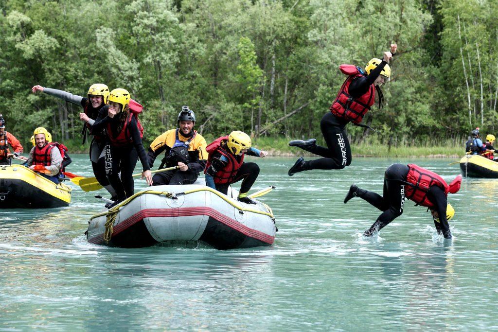 Eine Gruppe springt von ihrem Raft-Boot ins Wasser.