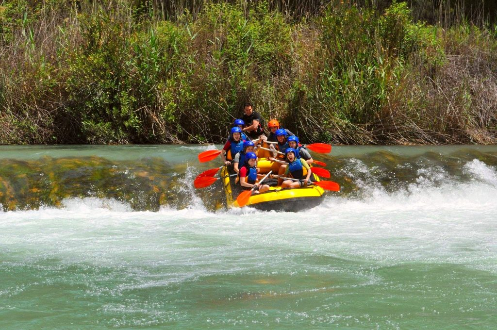 A rafting tour on the Cabriel River sliding down a small natural slide.