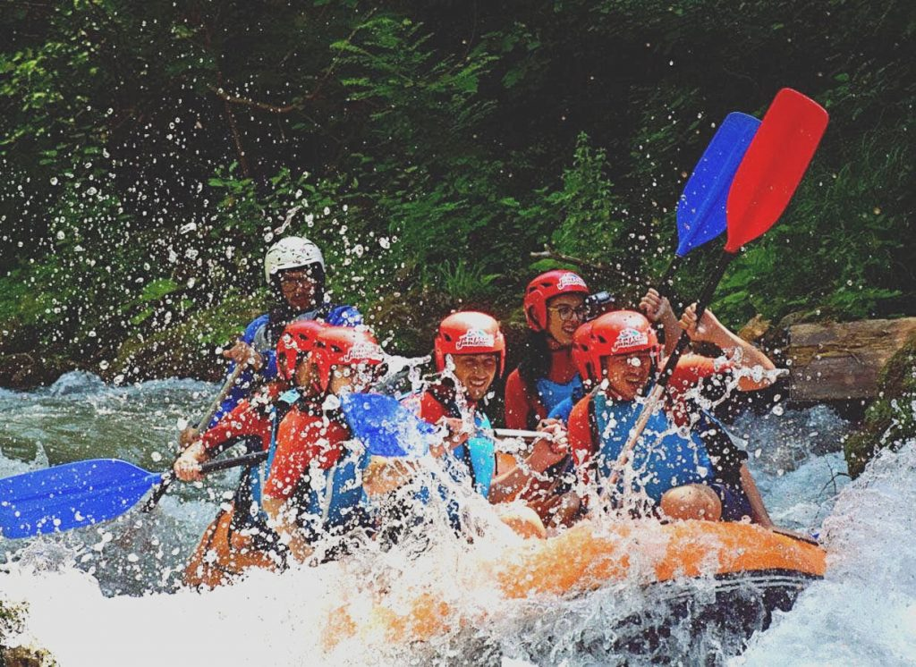 A fully manned raft boat going through rapids.