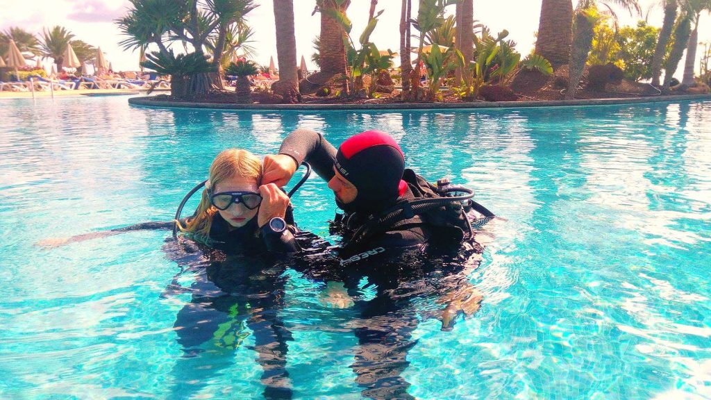 A child and its guide are doing a test dive in a pool before going scuba diving on the Canary Islands.