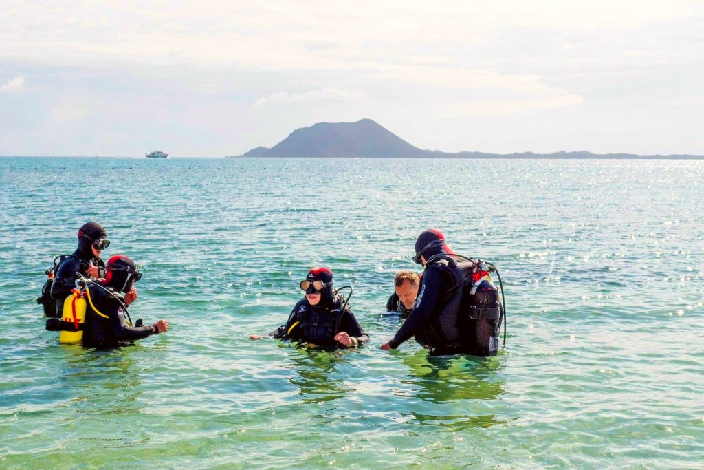 A group of people are trying scuba diving on the Canary Islands for the first time.