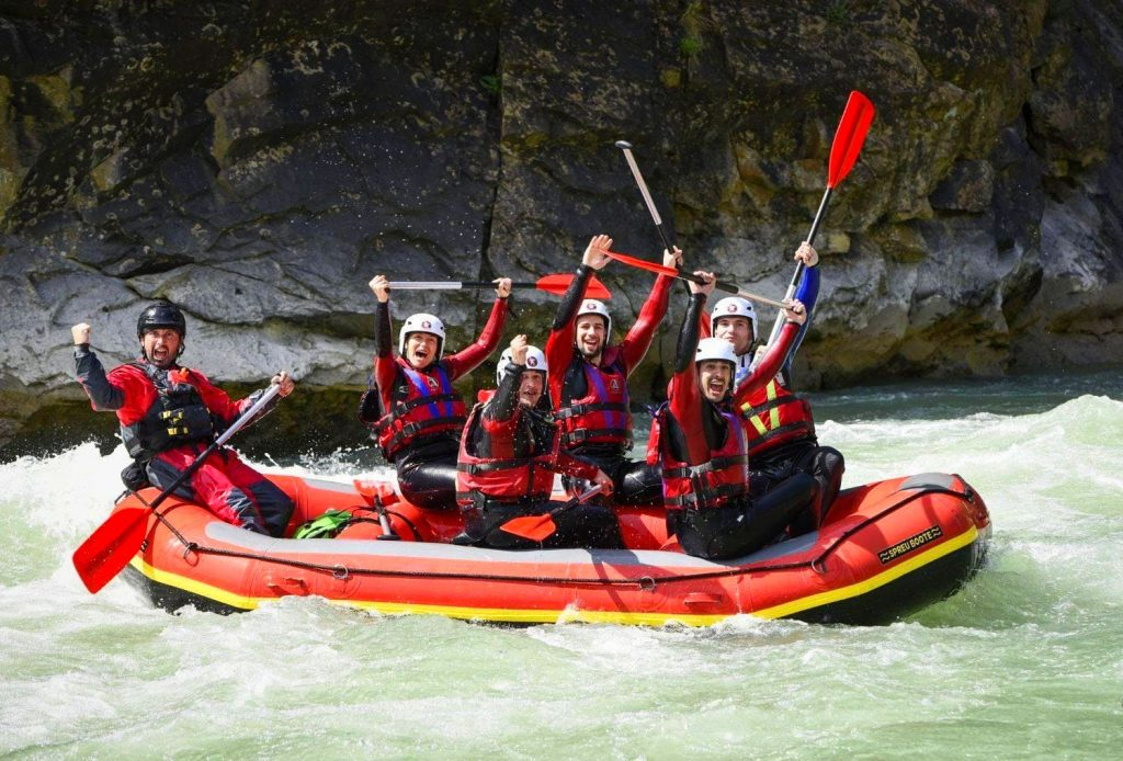 This rafting tour on the Gállego is going splendidly: the group and their guide are celebrating on their boat.