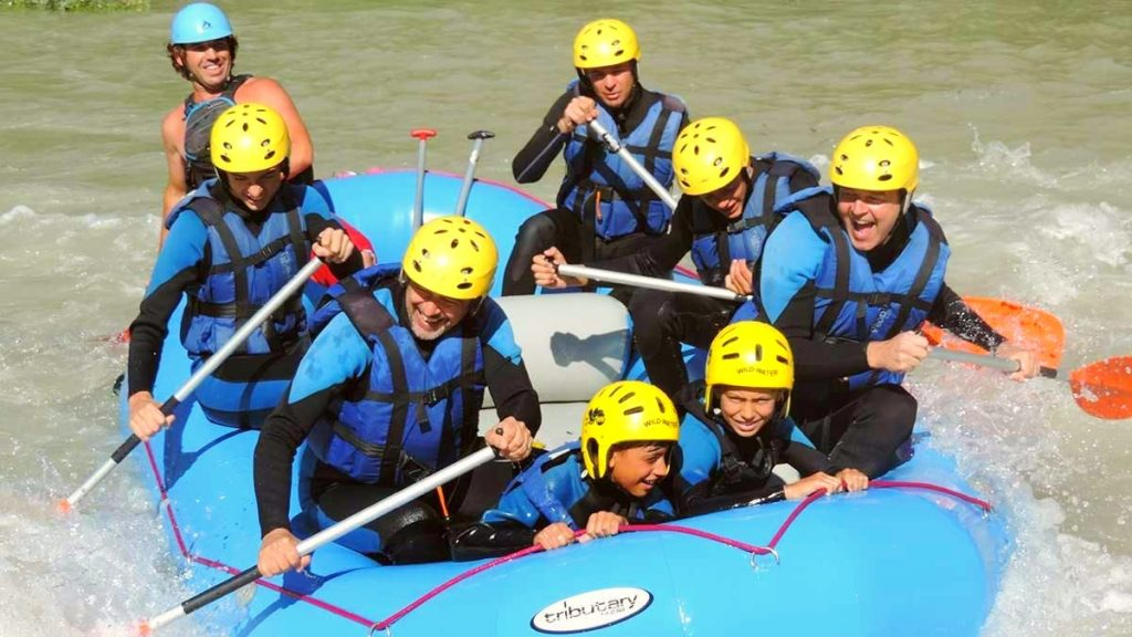 A rafting tour on the Genil during which children are holding on tight while adults are happily paddling.