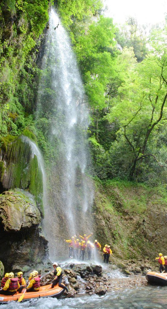 Eine Gruppe von Raftern genießt eine Pause bei einem Wasserfall.
