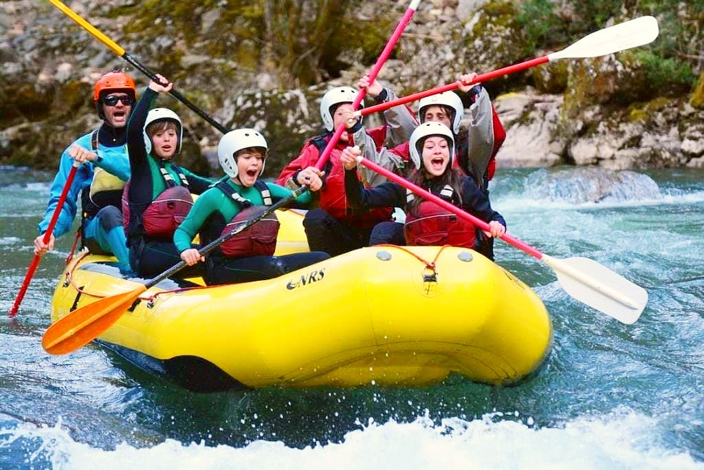 Children and their guide on a rafting tour on the Noguera Pallaresa about to go over a quite strong rapid.