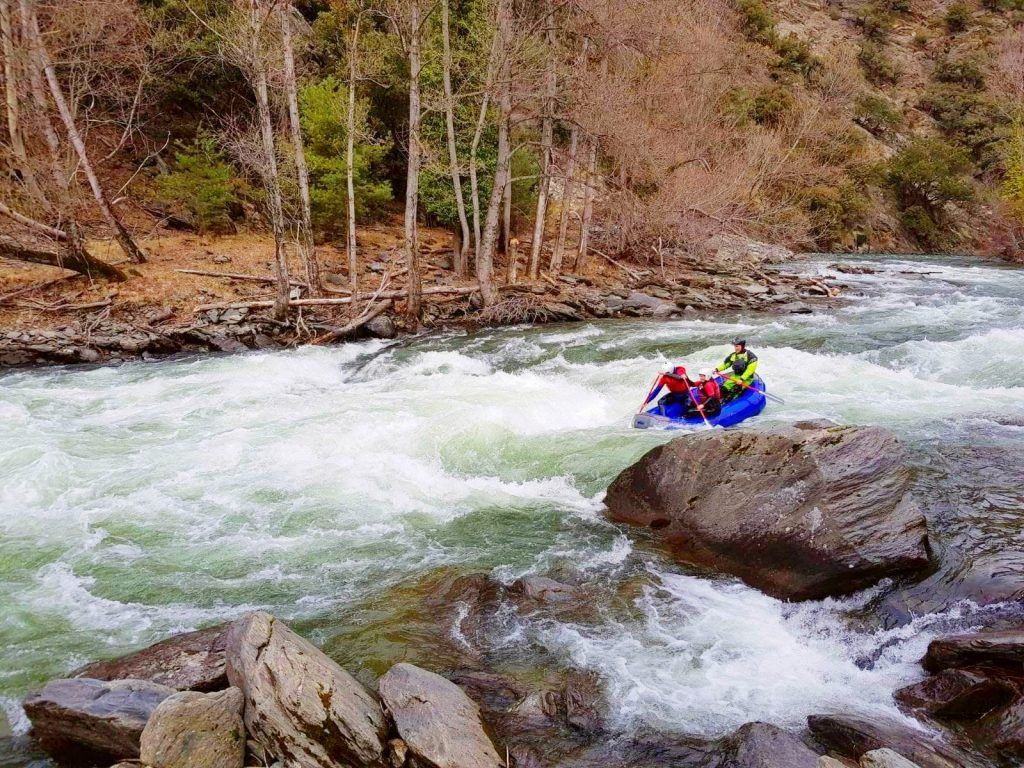 While on a rafting tour on the Noguera Pallaresa, a group of rafters paddle their way through strong rapids.
