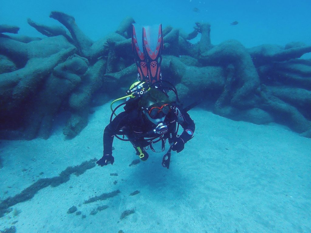 A diver is exploring an underwater museum while scuba diving on the Canary Islands.