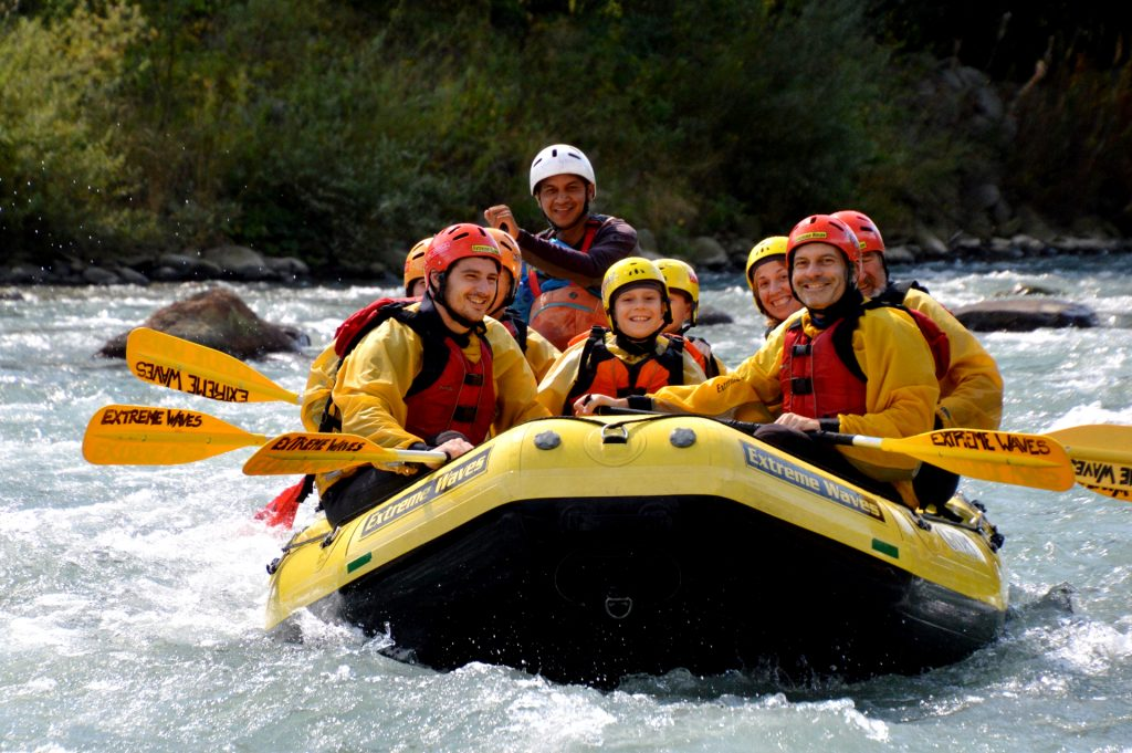 A group laughing while rafting on the Noce.
