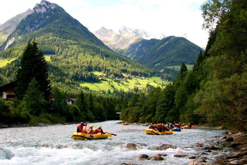 Eine Rafting-Gruppe bewundert die Berglandschaft im Hintergrund.