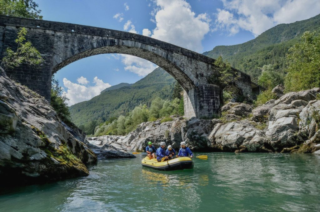 A group goes under an old stone bridge on their rafting tour.