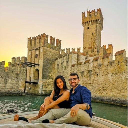 Una coppia posa su una barca al Lago di Garda al tramonto con il castello di Sirmione sullo sfondo.