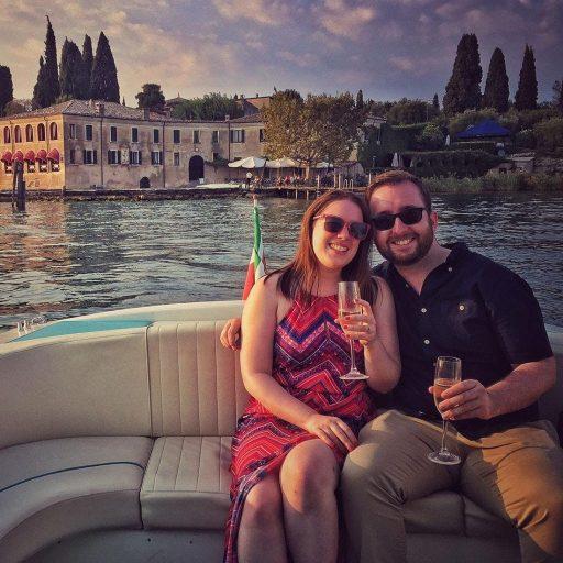 Una coppia fa una gita romantica in barca al Lago di Garda e prindano con del prosecco.