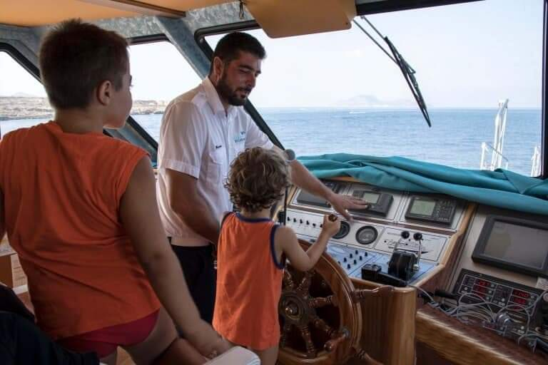 During a boat trip to the Aegadian Islands the captain shows the command cabin to 2 children.