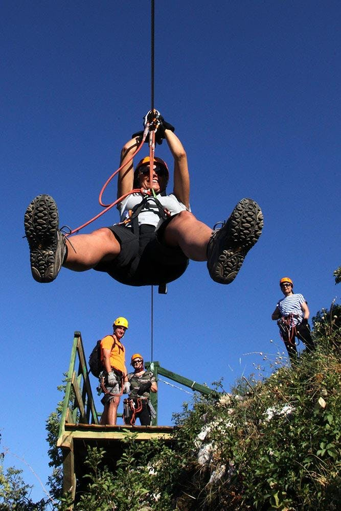 During a zipline adventure in Omiš, on the Cetina River, a woman is photographed from below.