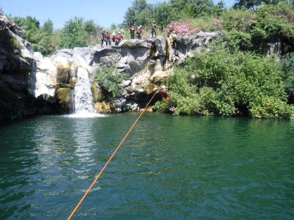 I partecipanti al tour di canyoning in Sicilia provano la zipline.