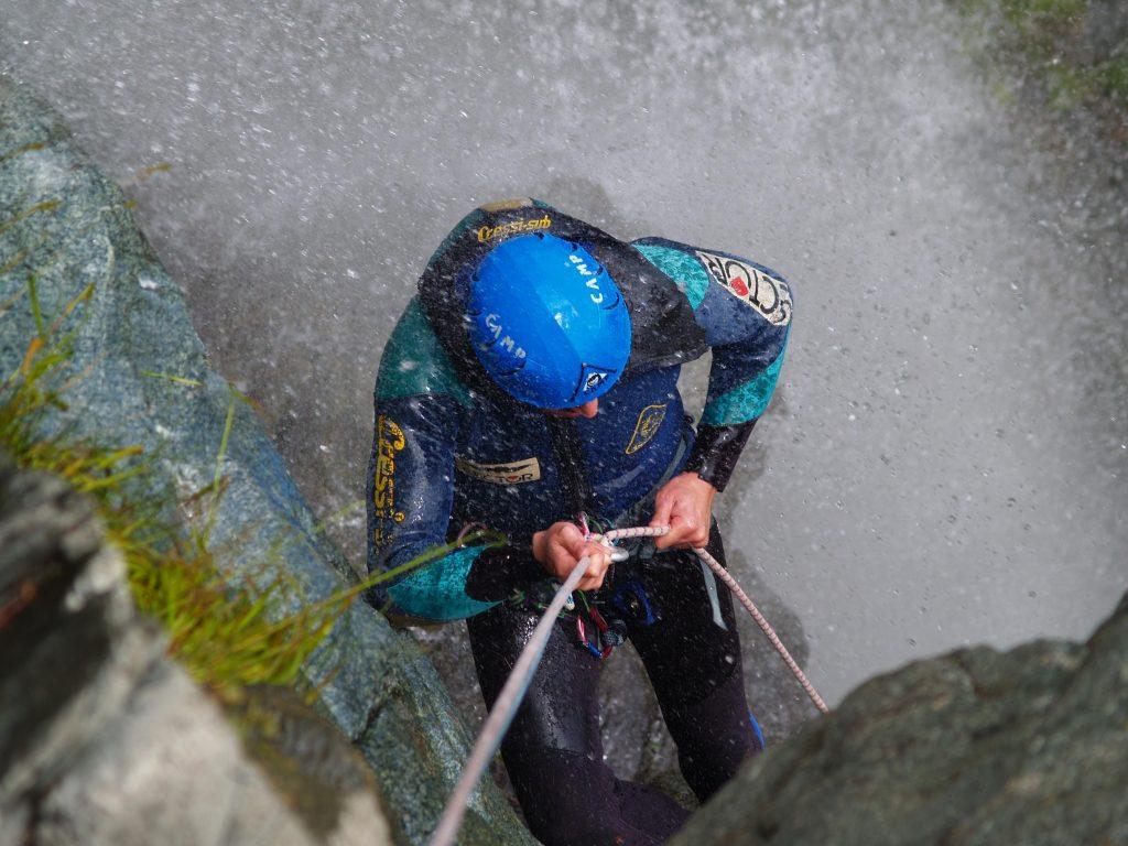 Durante un'escursione di canyoning nel Chalamy un a persona fa una discesa in corda doppia.