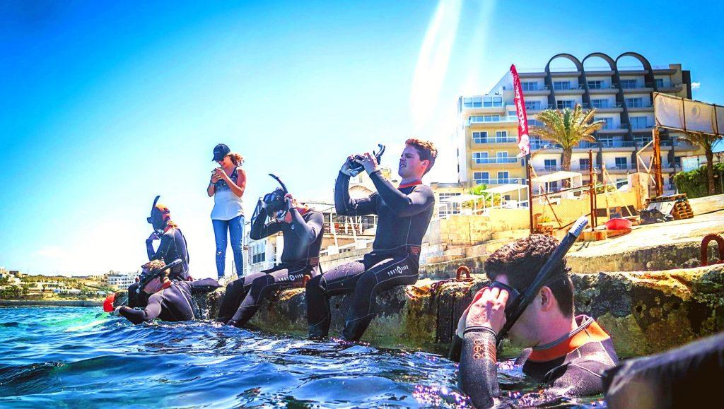 Un gruppo di 4 ragazzi si mette la maschera sul viso prima di un'escursione di snorkeling a Malta.