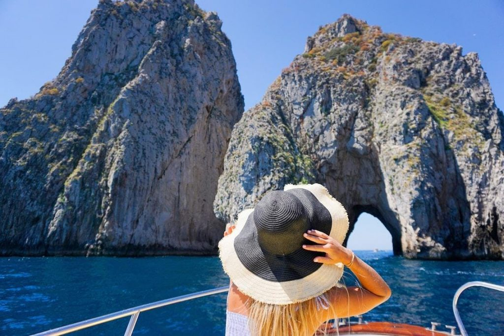 Eine Frau bewundert von ihrer Bootstour in Sorrent aus die Faraglioni.