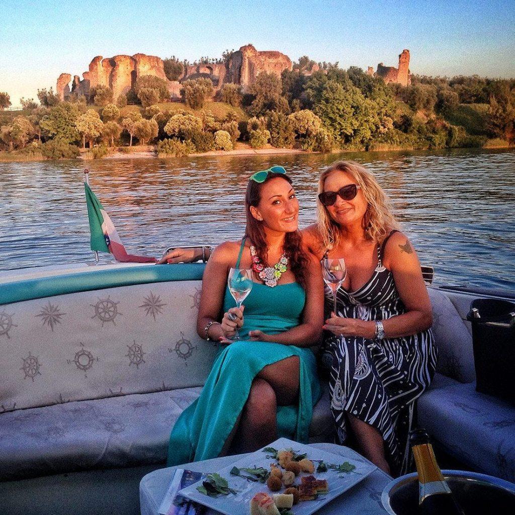 Ein Paar genießt auf einer Bootstour am Gardasee Prosecco und italienischen Snacks.