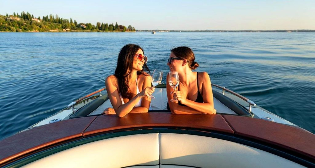 Zwei Frauen stoßen auf ihre Bootstour am Gardasee an.