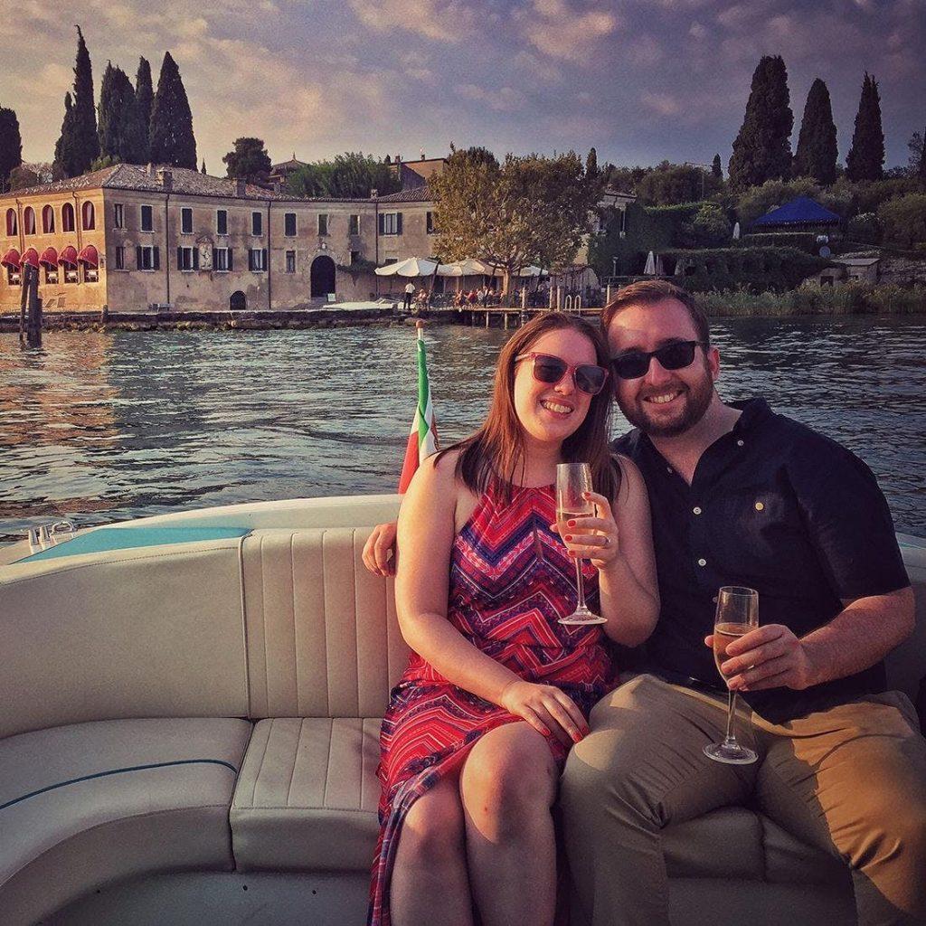 Ein Pärchen posiert auf ihrer Bootstour am Gardasee für ein Foto.