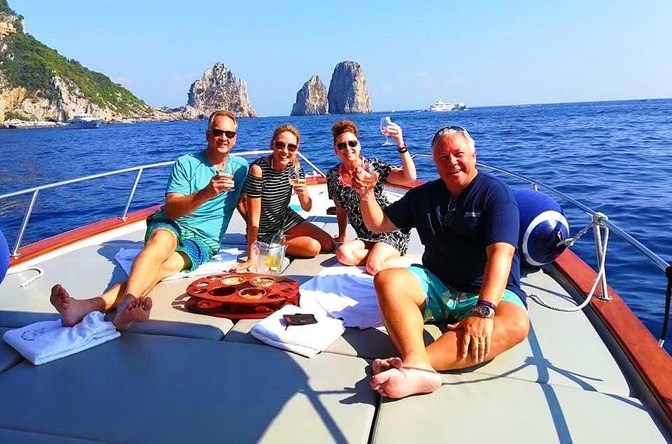 Zwei Paare stoßen mit Champagner auf ihre Bootstour in Sorrent an.