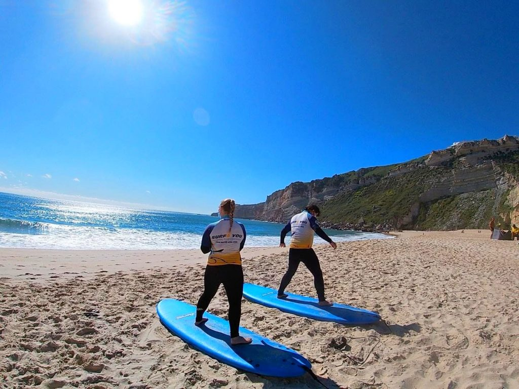 While surfing in Portugal, two people prepare for their lesson in Nazaré.