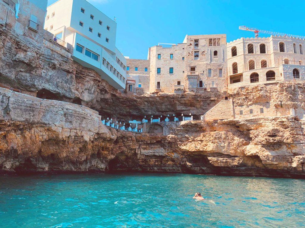 Un signore fa snorkeling a Polignano a Mare, oltre a lui si possono notare grotte e abitazioni.