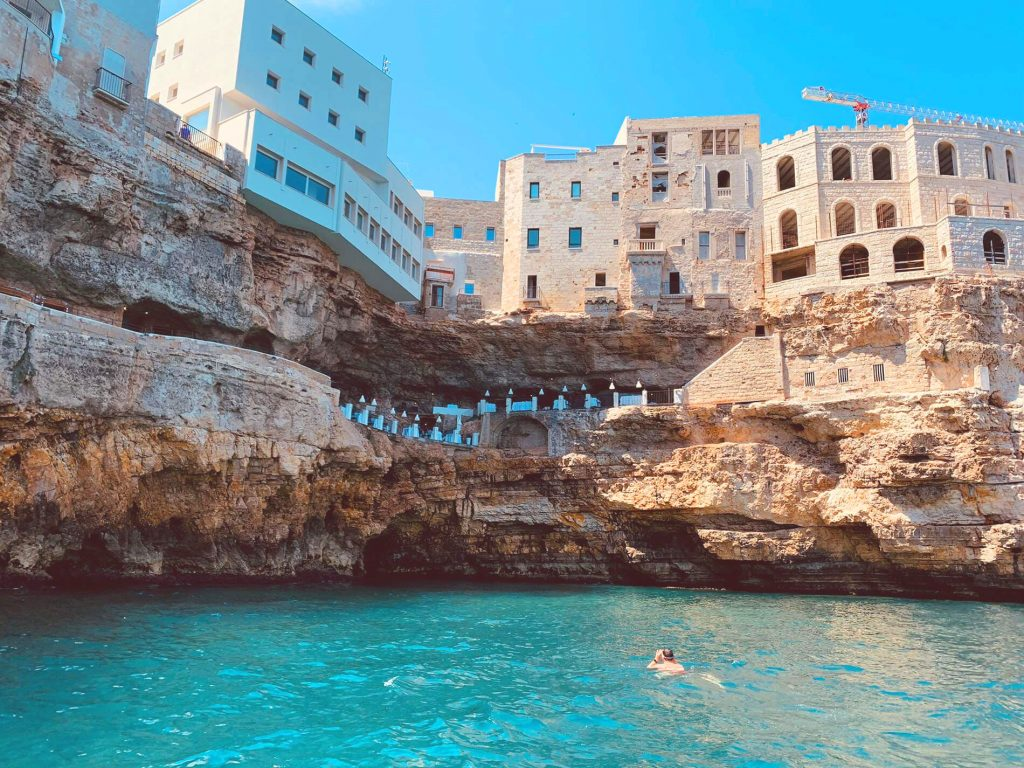 A man snorkeling in Polignano a Mare, beyond him you can see caves and houses.