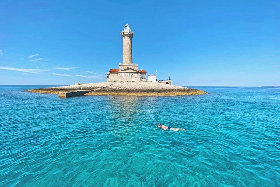 Ein von Wasser umgebener Leuchtturm kann beim Schnorcheln in Kap Kamenjak bewundert werden.