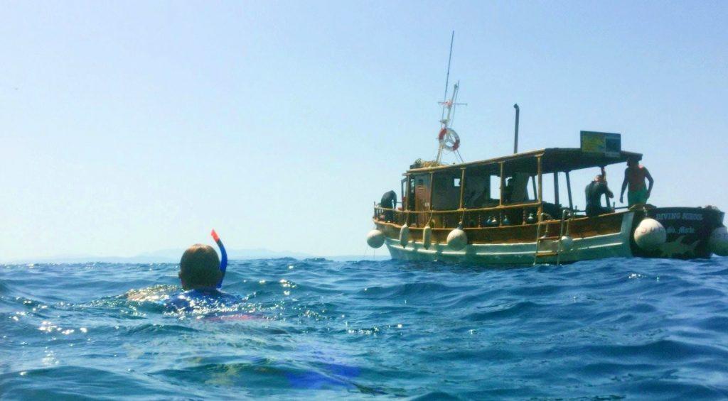 Ein Junge schwimmt in der Nähe eines Bootes beim Schnorcheln an der Makarska Riviera.