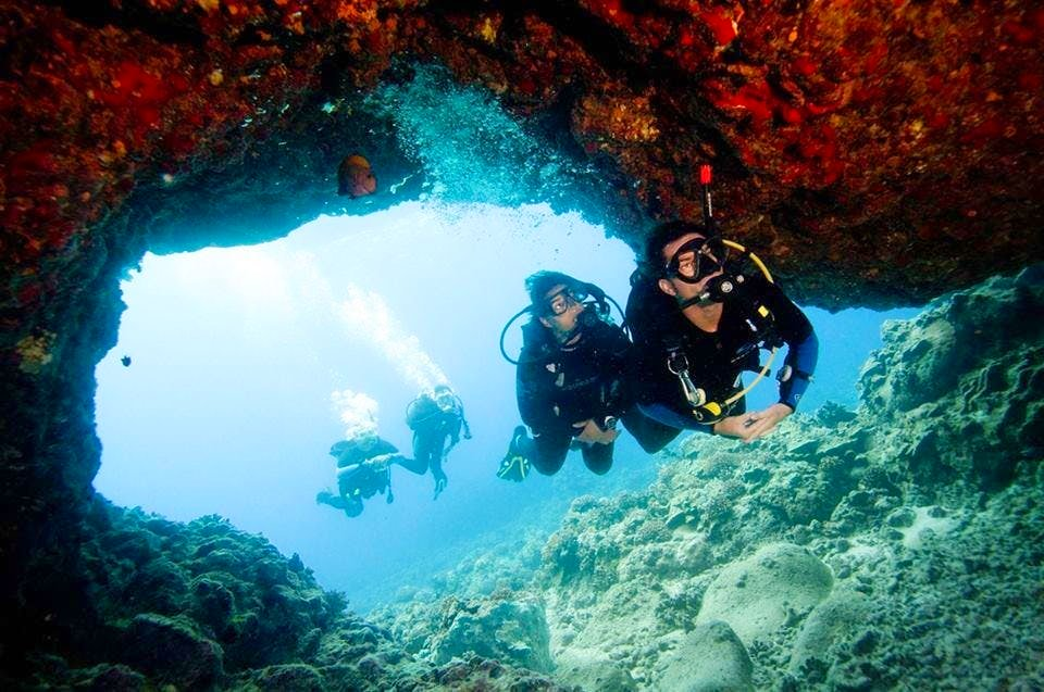 A group of divers exploring a cave while scuba diving in Spain.