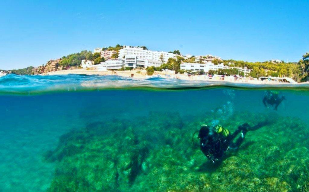 Two people are seen scuba diving in Spain, in Tossa de Mar.
