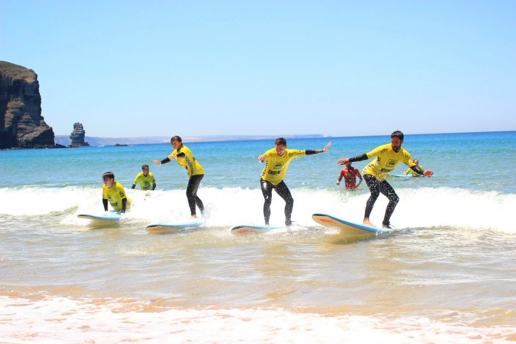 A group of beginners are surfing in Portugal,on a beach in Arrifana.