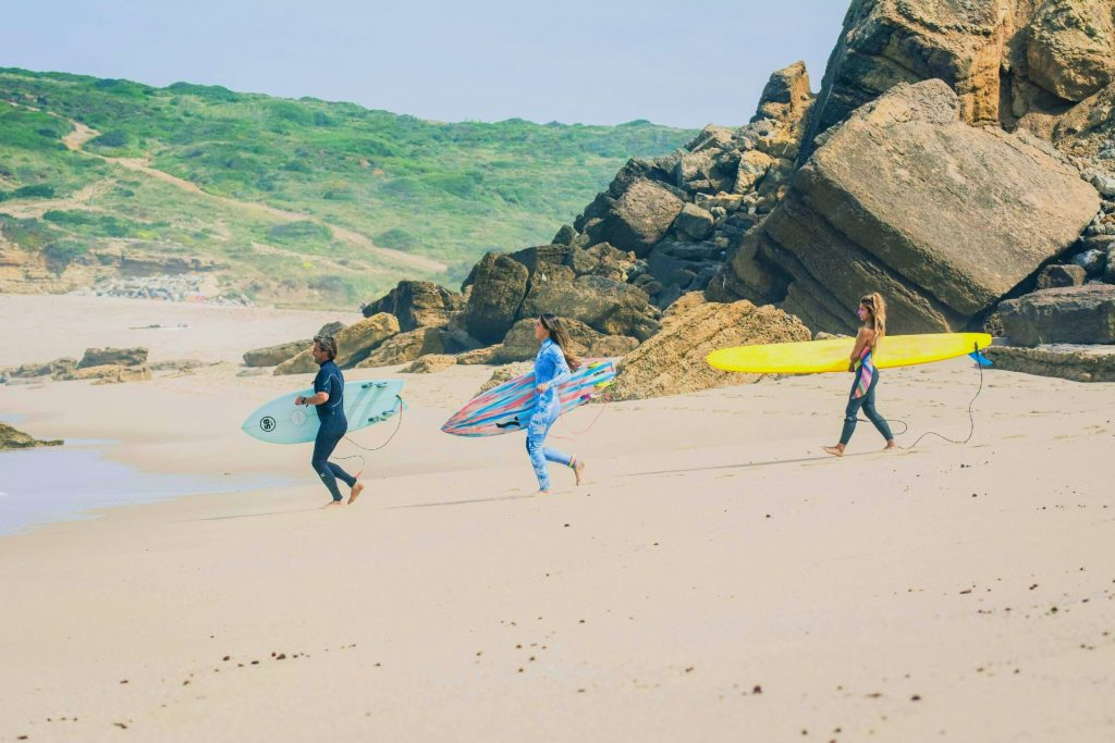 Three women about to go surfing in Portugal.