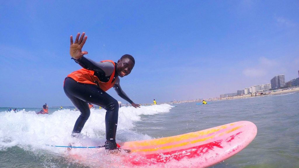 A boy is having fun while surfing in Portugal.