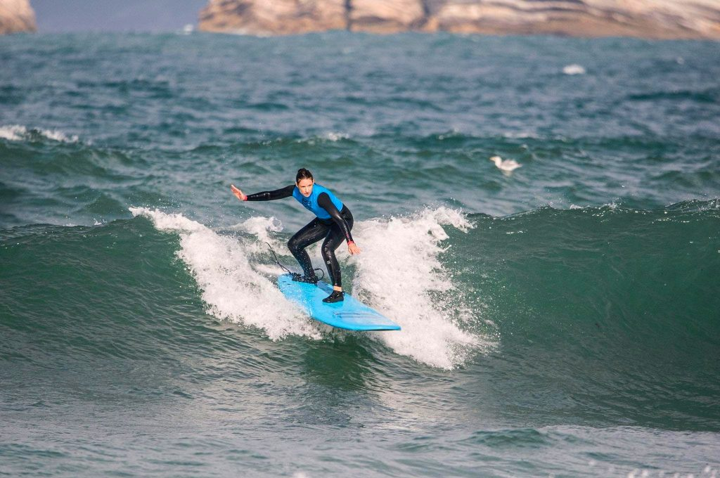 A young girl surfing in Portugal, on Gamboa Beach.