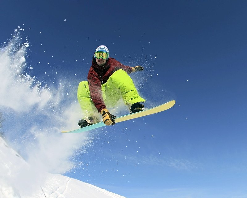 A snowboarder is doing some nice tricks on his snowboard during a day trip to La Pinilla from Madrid.