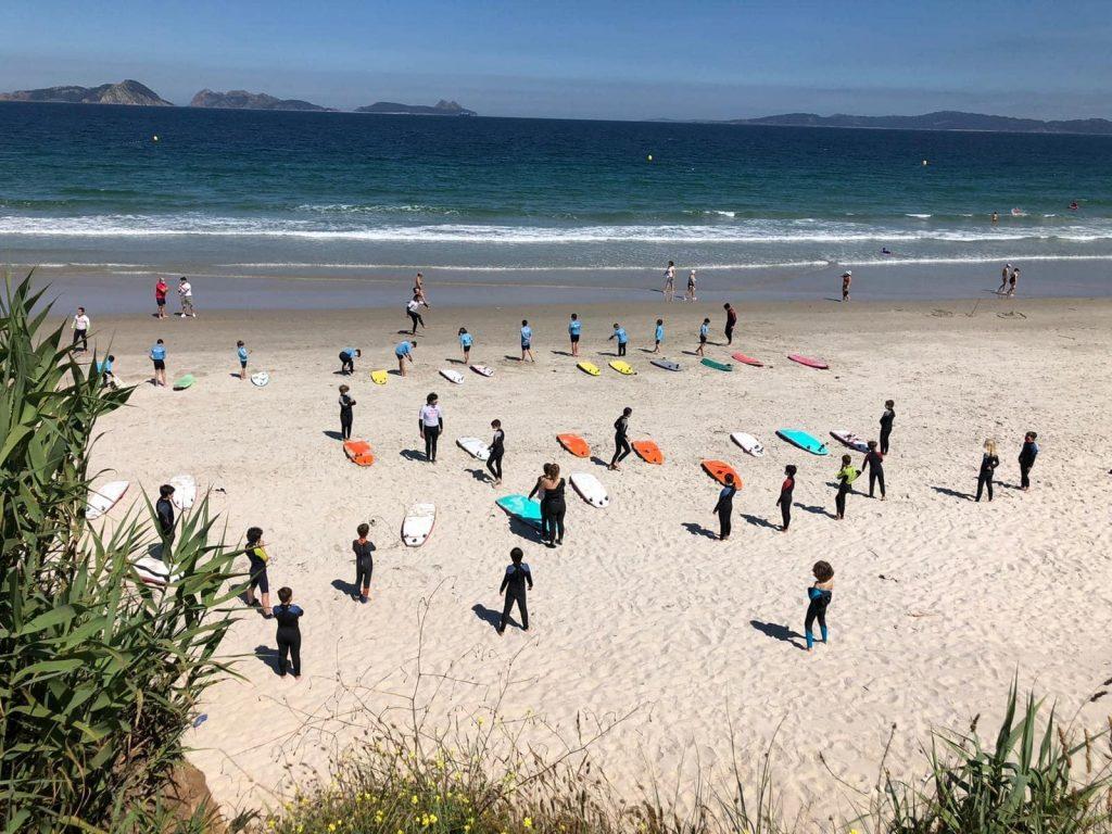 Mehrere Gruppen von Surfanfängerinnen nehmen an einem Surfkurs am Strand Praya La Lanzada teil.