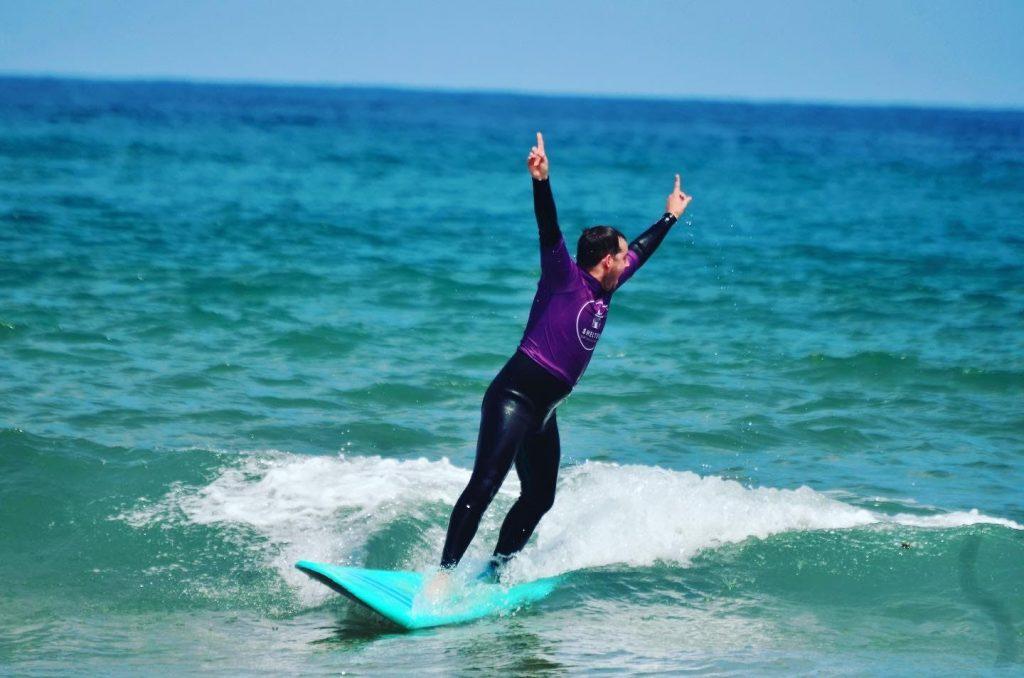 Ein Surfanfänger schafft es auf dem Surfbrett bei seiner ersten Surfstunde am Playa Zarautz in Spanien zu stehen.