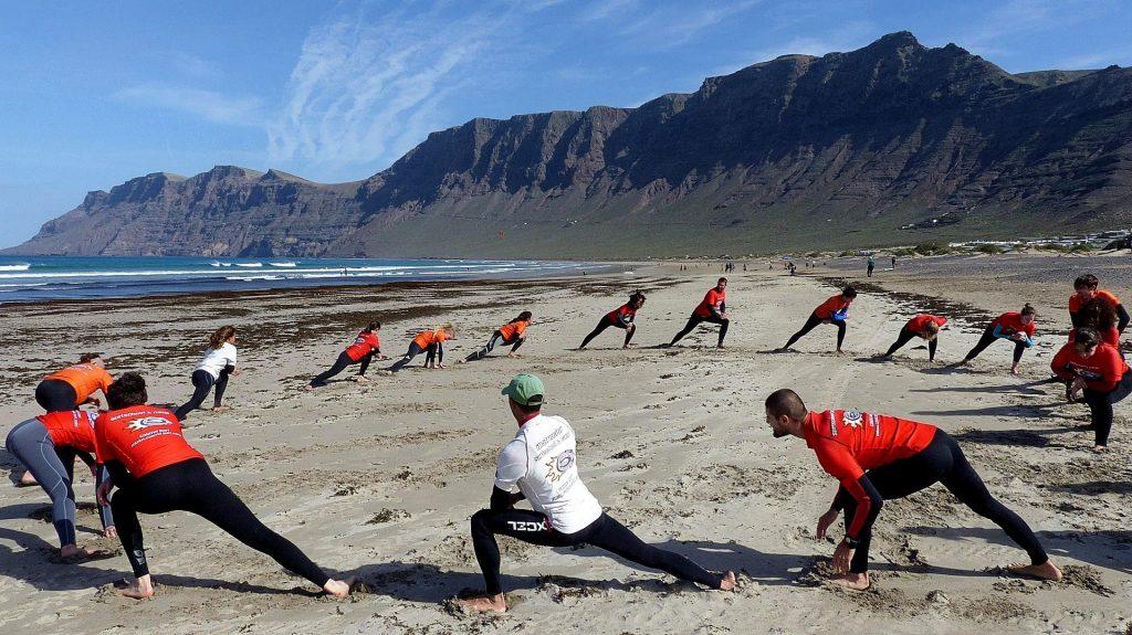 Während einer Surfstunde für Anfänger am Playa de Famara in Spanien wärmen sich die Teilnehmer auf.