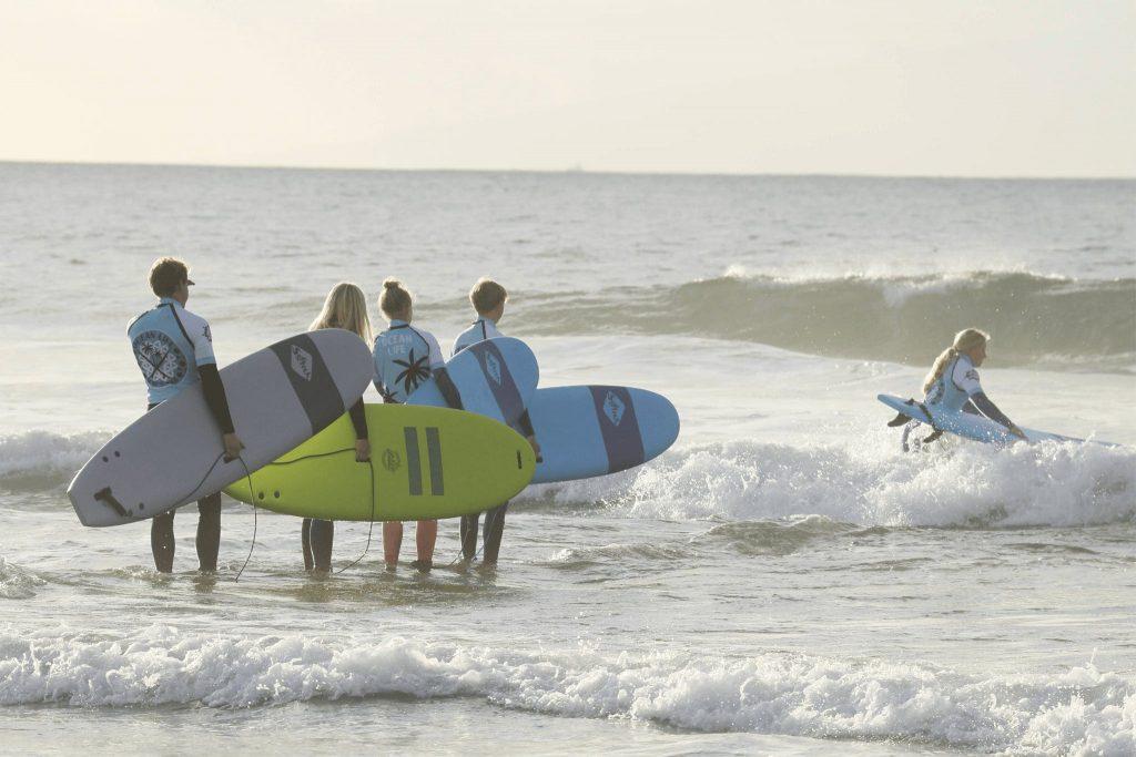 5 Surfanfänger nehmen lernen am Playa de Las Américas in Spanien surfen.