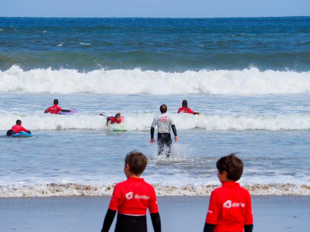 Zwei Kinder gehen während eines Surfkurses für Anfänger an der Playa de Patos in Spanien ins Wasser.