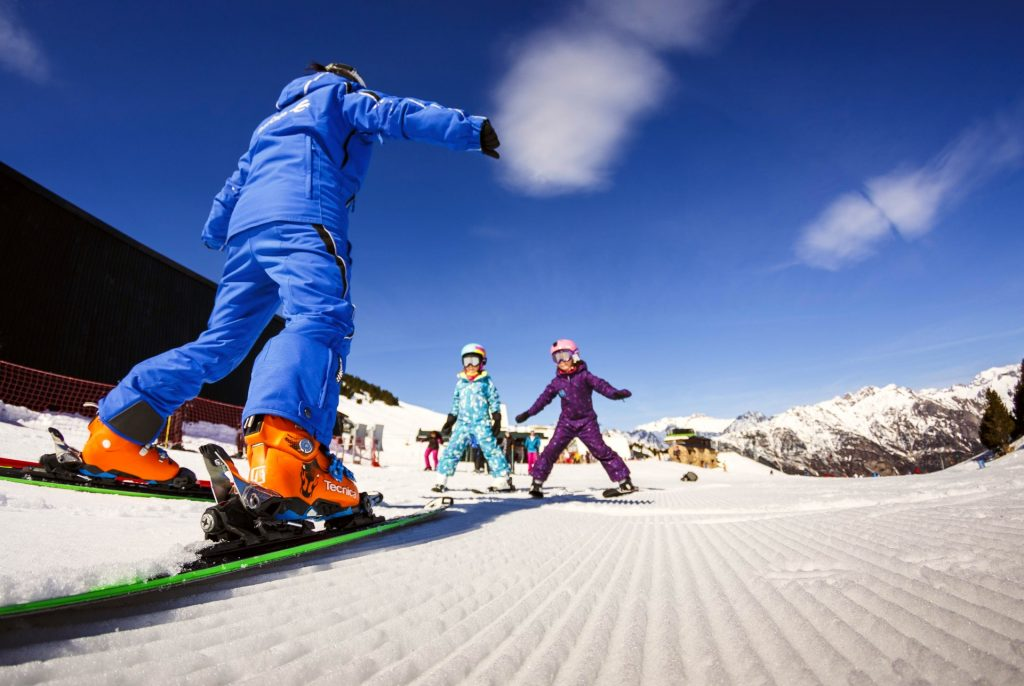 Two kids are learning how to ski in Aragon with a private ski instructor.